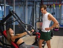 Sporty девушка делая вес работает на имитаторе с помощью ее личного тренера на спортзале скопируйте космос Стоковое Фото