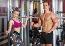 Sporty девушка и человек представляя в спортзале Стоковые Изображения RF