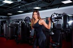 Sporty девушка поднимает бар Женщина брюнет фитнеса подходящая в острословии спортзала Стоковое фото RF