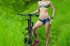 Sporty девушка с велосипедом Тонкое тело девушки с велосипедом Стоковое Изображение