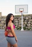 Sporty женщина играя баскетбол снаружи стоковые фото