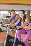 Sporty женщина используя задействуя велотренажер с ее partne фитнеса стоковое фото