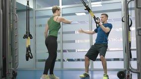 Sporty женщина и человек делая гимнастические тренировки или работая в классе фитнеса сток-видео
