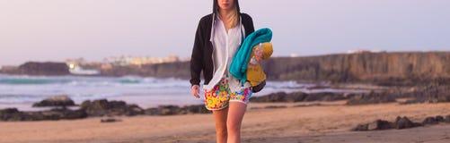 Sporty женщина идя на песчаный пляж в заходе солнца Стоковые Фото
