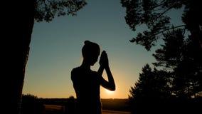Sporty женщина моля в парке на заходе солнца стоковое фото