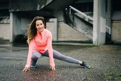 Sporty женщина на городской протягивая разминке фитнеса стоковая фотография rf