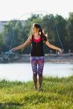 Sporty женщина на побережье озер делает тренировку используя веревочку скачки на заходе солнца Стоковое Фото