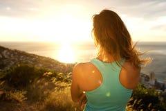 Sporty женщина от заднего наблюдающ заход солнца Стоковые Изображения RF