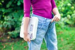 Sporty женщина показывая большие брюки и держа масштабы Потеря веса c стоковая фотография