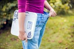 Sporty женщина показывая большие брюки и держа масштабы Потеря веса c стоковые изображения rf
