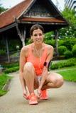 Sporty женщина получая готовый для бежать на парке города Стоковая Фотография