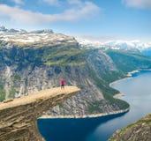 Sporty женщина представляя на Trolltunga Норвегии Стоковая Фотография