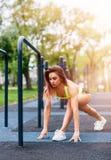 Sporty женщина при совершенное атлетическое тело протягивая в парке стоковое изображение rf