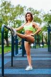 Sporty женщина при совершенное атлетическое тело протягивая в парке стоковое фото rf