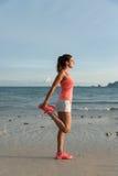 Sporty женщина протягивая перед бежать Стоковое Фото