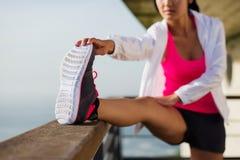 Sporty женщина протягивая перед бежать стоковая фотография