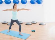 Sporty женщина протягивая руки в студии фитнеса Стоковые Фотографии RF