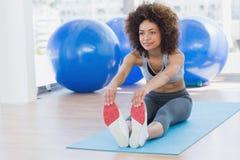 Sporty женщина протягивая руки к ногам в студии фитнеса Стоковое Изображение