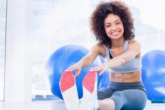Sporty женщина протягивая руки к ногам в студии фитнеса Стоковое фото RF
