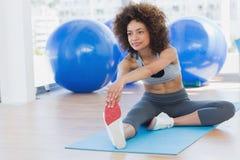 Sporty женщина протягивая руки к ноге в студии фитнеса Стоковая Фотография