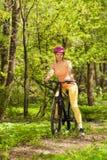 Sporty женщина с горным велосипедом на следе полесья Стоковое Фото