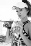 Sporty женщина с питьевой водой скейтборда против неба Стоковые Изображения RF