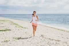 Sporty женщина jogging с небесами и морем на предпосылке стоковое изображение rf