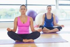 2 sporty женщины в лотосе представляют на студии фитнеса Стоковые Фото