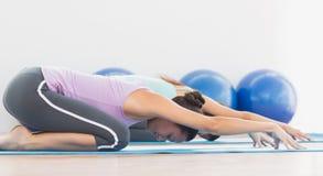 2 sporty женщины в раздумье представляют на студии фитнеса Стоковое фото RF