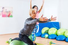 Sporty женщины делая протягивающ тренировки с шариком стабильности фитнеса в спортклубе стоковое изображение rf