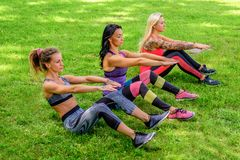 3 sporty женщины делая разминки abs стоковая фотография