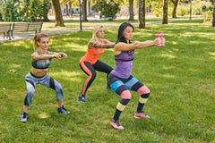 3 sporty женщины делая сидения на корточках в парке стоковые фото