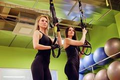 2 sporty женщины делая trx связывают тренировки в спортзале Стоковое фото RF