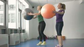 Sporty женщины делая гимнастические тренировки или работая в классе фитнеса сток-видео