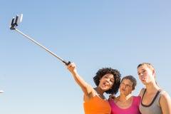 Sporty женщины представляя и принимая selfies с selfiestick Стоковое фото RF