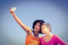 2 sporty женщины представляя и принимая selfies Стоковое фото RF