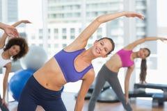 Sporty женщины протягивая руки на занятиях йогой Стоковые Изображения