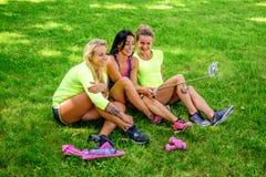 3 sporty женщины сидя на лужайке и делая selfie стоковое изображение rf