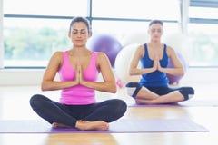 2 sporty женщины сидя с соединенными руками на студии фитнеса Стоковое Изображение RF