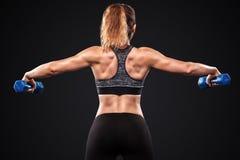 Sporty и подходящая красивая женщина с гантелью работая на черной предпосылке для того чтобы остаться подходящий Мотивировка разм Стоковые Фото