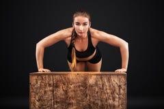 Sporty красивая женщина работая на черной предпосылке для того чтобы остаться подходящий Мотивировка разминки Стоковые Фотографии RF