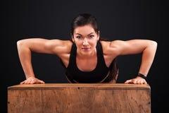Sporty красивая женщина работая на черной предпосылке для того чтобы остаться подходящий Мотивировка разминки Стоковое Изображение