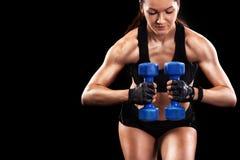Sporty красивая женщина с гантелью работая на черной предпосылке для того чтобы остаться подходящий Мотивировка разминки Crossfit Стоковые Изображения
