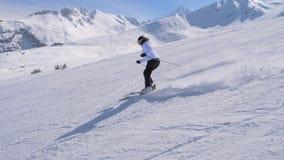 Sporty лыжник женщины профессионально высекая вниз с наклона в горы Стоковые Изображения