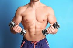 Sporty молодой человек с гантелями на крупном плане предпосылки цвета Стоковая Фотография RF