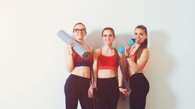 Sporty молодые женщины стоя против стены Резвит предпосылка 3 девушки фитнеса в спортзале после разминки скопируйте космос Женщин стоковые изображения rf