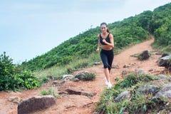 Sporty молодая женщина в черном следе sportswear бежать на пути природы горы Подходящая девушка jogging покатый скалистый след Стоковая Фотография RF
