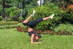 Sporty молодая женщина делая тренировку handstand с гнуть ногами на траве в парке Йога подходящей девушки практикуя outdoors Стоковые Изображения