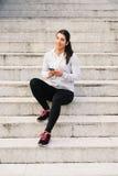 Sporty молодая женщина отправляя СМС на smartphone стоковое фото