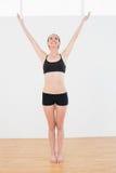 Sporty молодая женщина протягивая руки в студии фитнеса Стоковое Фото